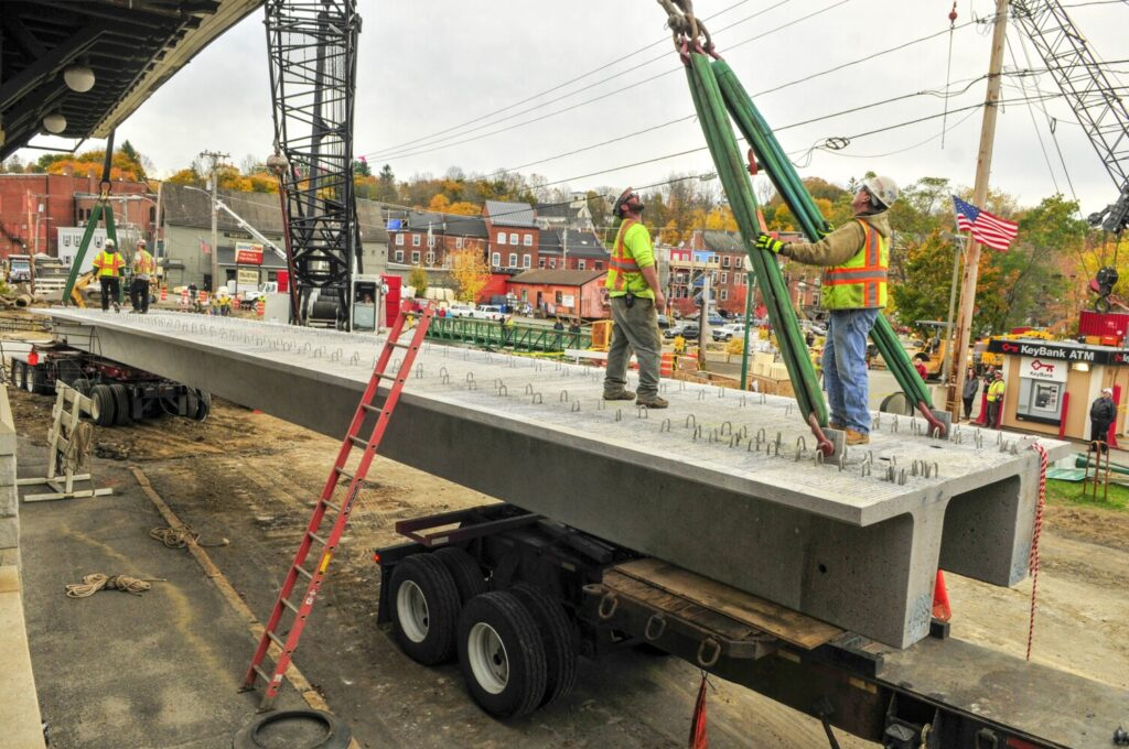 Workers rig straps from a large crane to the first of the new bridge supports put into place over Cobbossee Stream in downtown Gardiner in October. A commission formed to recommend new funding options for transportation projects will ask for more time to draft a long-term solution.