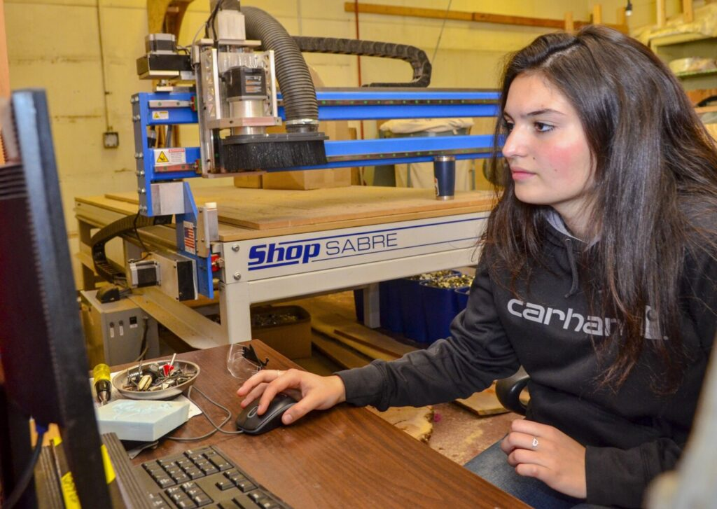 Sydney Birtwell sits at the computer that controls the CNC router behind her on Oct. 4 in the industrial arts wing of Maranacook Community High School. Birtwell set it up to cut many field hockey stick silhouettes on a sheet of plywood.