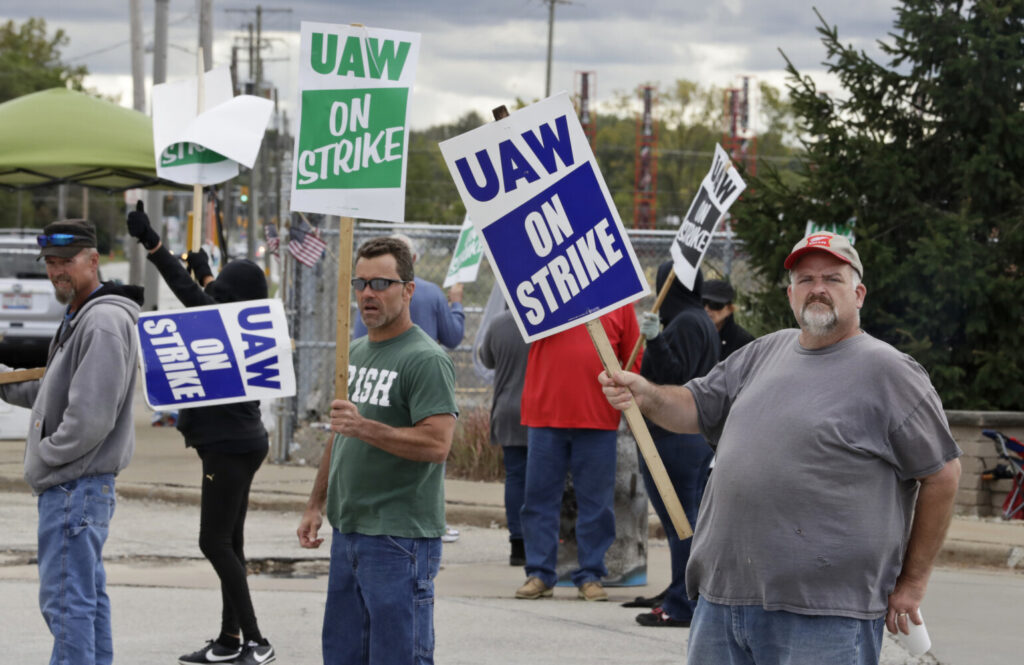 John Kirk, right, a 20-year-employee, pickets with co-workers Oct. 4 outside the General Motors Fabrication Division in Parma, Ohio. The strike ended Oct. 25 after the union agreed to a new contract with GM.