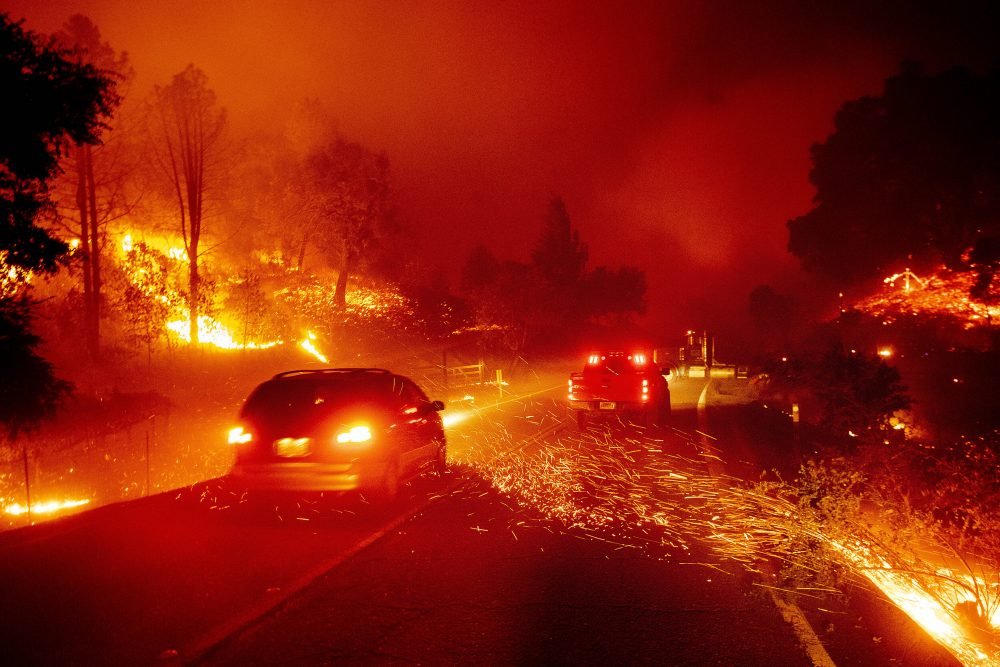 Embers fly across a roadway as the Kincade Fire burns through the Jimtown community of Sonoma County, Calif., on Thursday.