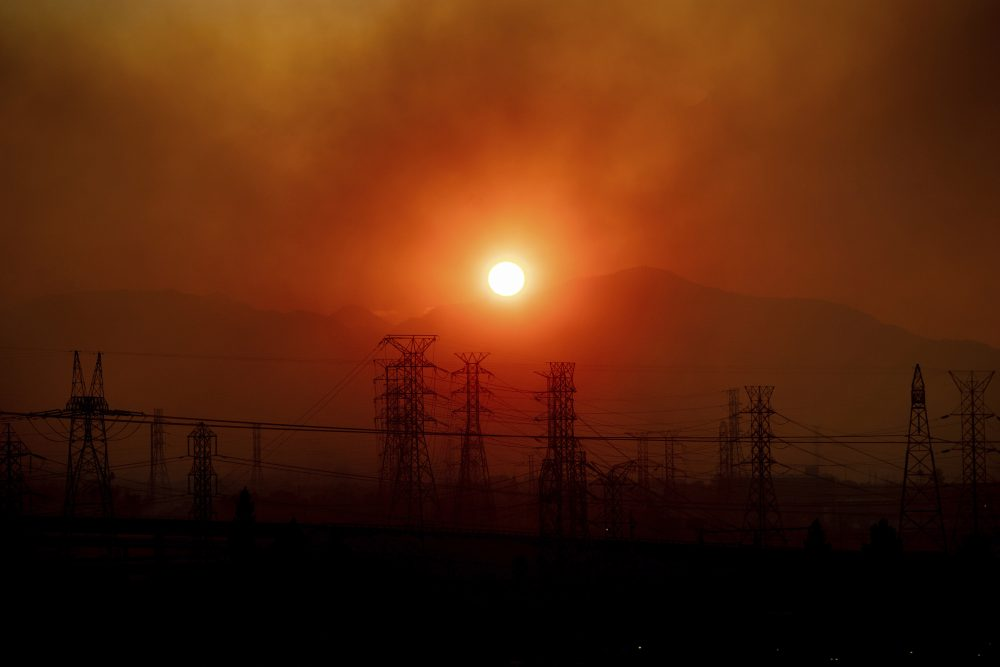 Smoke from the Saddleridge Fire hangs above power lines as the sun rises in Newhall, Calif., on Friday.
