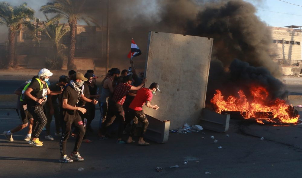 """Anti-government protesters set fires and close a street during a demonstration in Baghdad, Iraq, Friday. Security forces opened fire at hundreds of anti-government demonstrators in central Baghdad, killing some protesters and injuring dozens, hours after Iraq's top Shiite cleric warned both sides to end four days of violence """"before it's too late."""""""