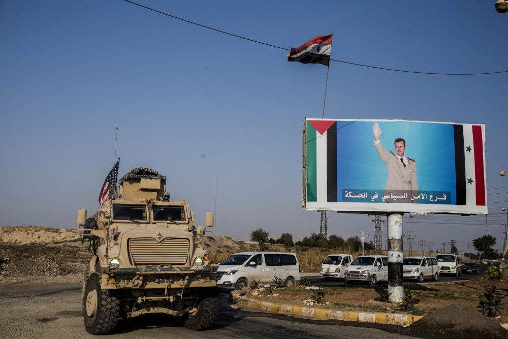 A U.S. military convoy drives through the town of Qamishli, north Syria, past a poster showing Syrian President Bashar Aassad on Saturday.  Baderkhan Ahmad/Associated Press