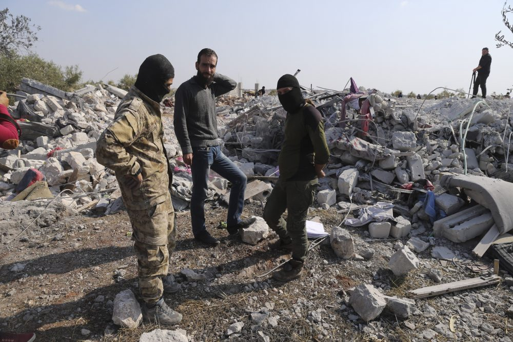People look at a destroyed houses near the village of Barisha, in Idlib province, Syria, on Sunday after an operation by the U.S. military which targeted Abu Bakr al-Baghdadi, the shadowy leader of the Islamic State group.