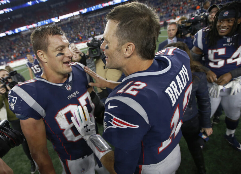 Former New England Patriots tight end Rob Gronkowski, left, and quarterback Tom Brady speak at midfield after beating the Kansas City Chiefs last October in Foxborough, Mass. The Patriots have reportedly agreed to trade Gronkowski, who retired after the 2018 season, to Tampa Bay so he can reunite with Brady.