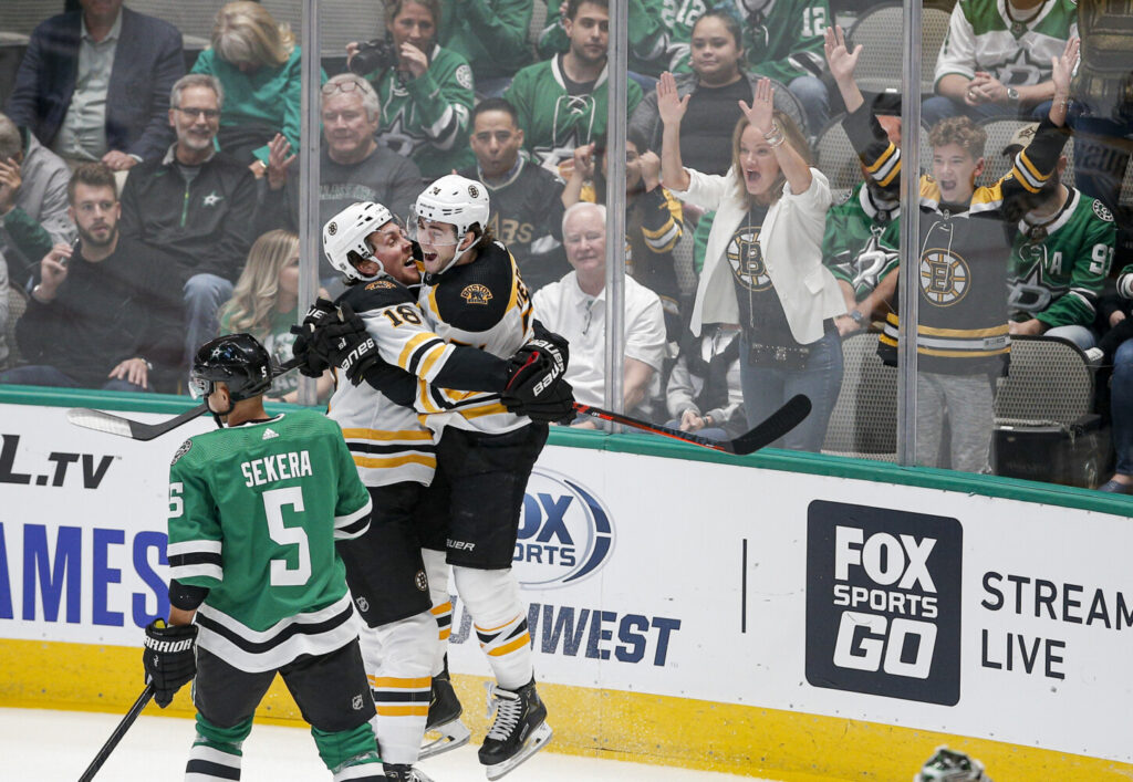 Dallas Stars defenseman Andrej Sekera skates past as Boston Bruins forward Brett Ritchie, 18, is congratulated by forward Jake DeBrusk after scoring a goal during the first period of the Bruins' 2-1 win Thursday in Dallas.