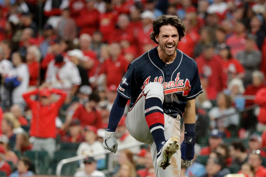 Atlanta Braves' Dansby Swanson celebrates after scoring during the ninth inning of the Braves' 3-1 win over the Cardinals in Game 3 of the NLDS on Sunday in St. Louis.