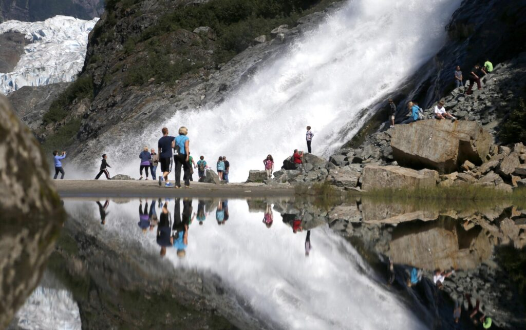 Tourist at the Mendenhall Glacier in the Tongass National Forest are reflected in a pool of water as they make their way to Nuggett Falls in 2013 in Juneau, Alaska. The Trump administration Tuesday proposed allowing logging on more than half of the 16.7 million-acre Tongass, the largest intact temperate rainforest in North America.
