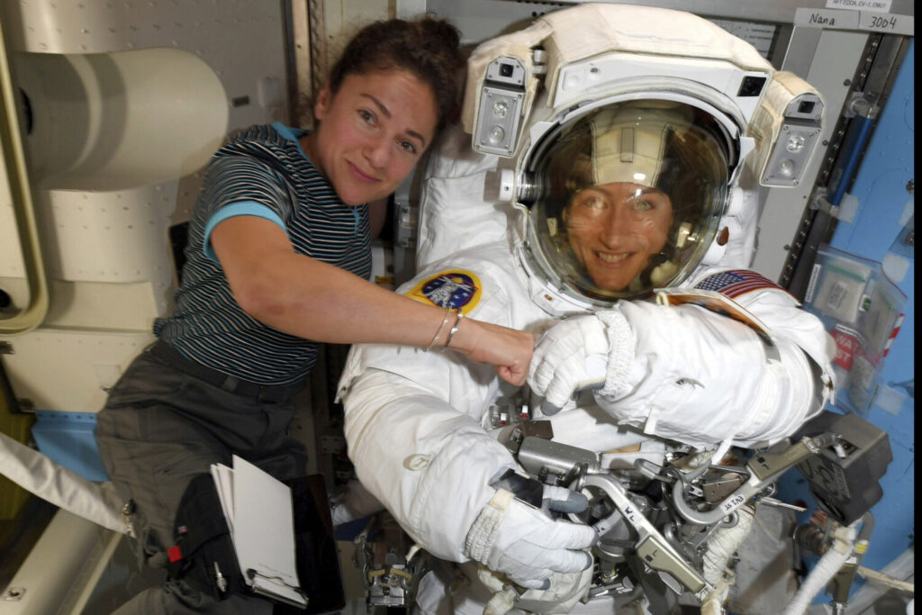 In this image released Oct. 4 by by NASA, astronauts Christina Koch, right, and Jessica Meir pose for a photo on the International Space Station. NASA has scheduled the first all-female spacewalk Friday after a power system failure on the International Space Station.