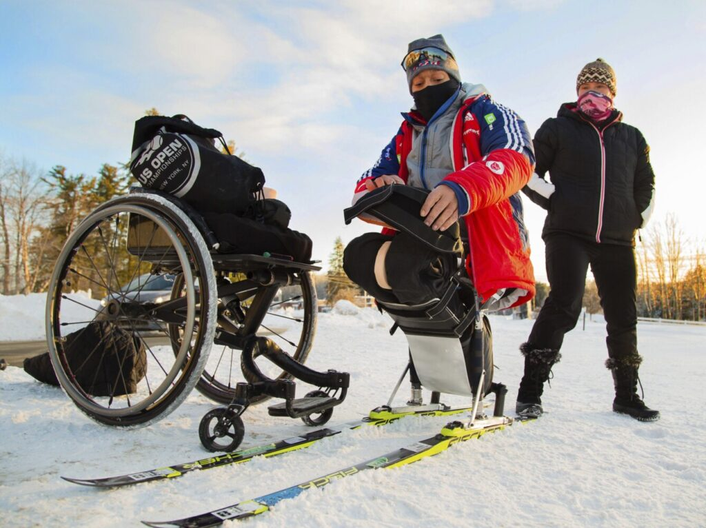 Paralympic hopeful Eric Frazier straps into his adaptive cross country skis, as Kristina Sebastianski the director of the Pineland Farms' Veterans Adaptive Sports & Training, keeps him from sliding. Frazier, a former Marine, was training for the Nordic skiing event at the Outdoor Center at Pineland Farms in New Gloucester on Dec. 28, 2017.