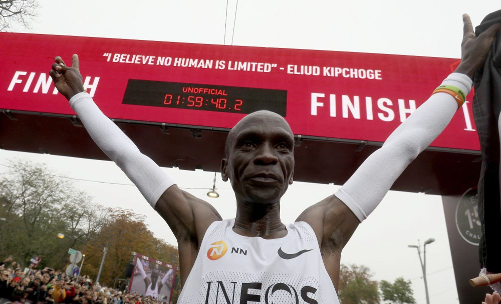 Marathon runner Eliud Kipchoge from Kenya celebrates under the clock after crossing the finish line of the INEOS 1:59 Challenge after 1:59:40 in Vienna on  Saturday. He is the first human ever to run a marathon under two hours.