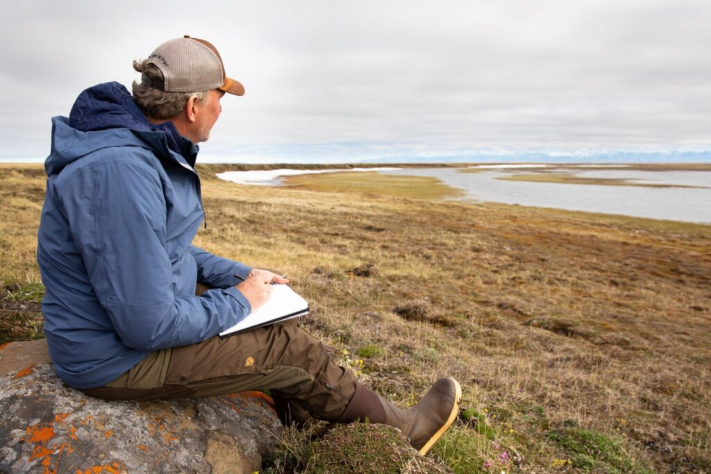 "Wildlife artist Michael Boardman of North Yarmouth sketches on the tundra in the Arctic National Wildlife Refuge, where he served as artist in residence for 10 days in June. ""It's so terrible to destroy this place in any way, shape or form,"" he said."