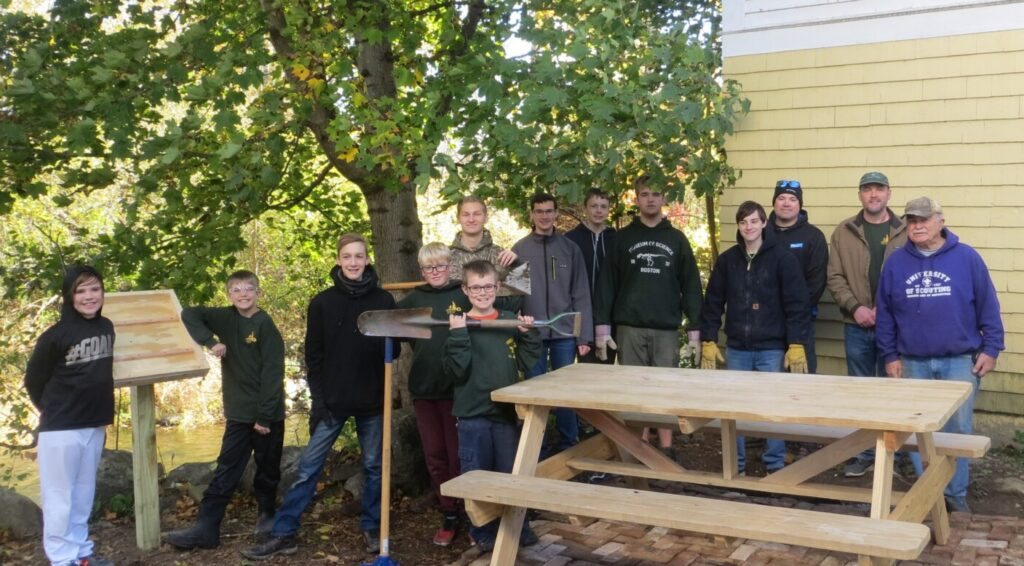 The brick pad, the picnic table and sign placard near the Outlet Stream are part of Ben Legasse's Eagle Scout Project. From left are Kameron Rossignol, Kasen Kelley, Remy Pettengill, Ayden Newell and Caleb Knock. Back from left are Ben Lagasse, Aiden Pettengill, Hunter Praul, Kaiden Kelley, Michael Boostedt, Leaders Derek Rossignol, Darryl Praul and Ron Emery. Also helping, though not in photo, were Leaders Lee Pettengill and parents Keith Lagasse, Jonathan Knock and Grange member Bernie Welch.