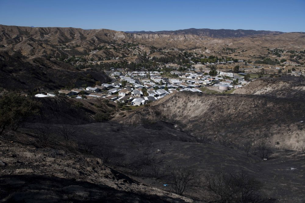 A mobile home community sits between charred hillsides from the Tick Fire on Thursday in Santa Clarita, Calif.