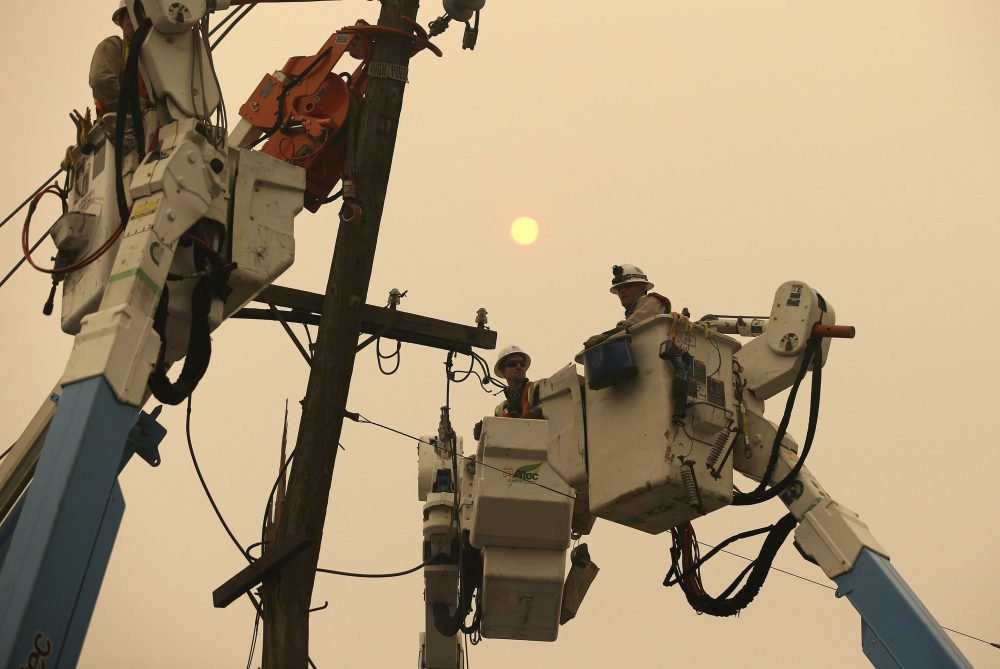 Pacific Gas & Electric crews work to restore power lines in Paradise, Calif., on Nov. 9, 2018. Two years to the day after some of the deadliest wildfires tore through Northern California wine country, two of the state's largest utilities were poised Tuesday to shut off power to more than 700,000 customers in 34 counties, in what would be the largest preventive shut-off to date as utilities try to head off wildfires caused by faulty power lines.
