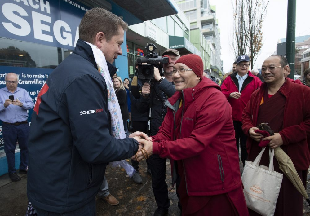 A Tibetan monk shakes hands with Conservative leader Andrew Scheer outside a campaign office in Vancouver, British Columbia, Sunday, Oct. 20, 2019.