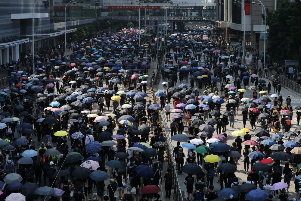 Anti-government protesters holding umbrellas march past police headquarters in Hong Kong, Tuesday, Oct. 1, 2019.