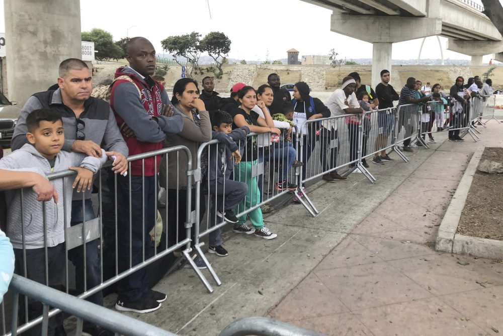 Asylum seekers in Tijuana, Mexico, listen to names being called from a waiting list to claim asylum at a border crossing in San Diego on Sept. 26. The number of migrants currently held in CBP custody is approximately 4,000, down from 19,000 in early June.