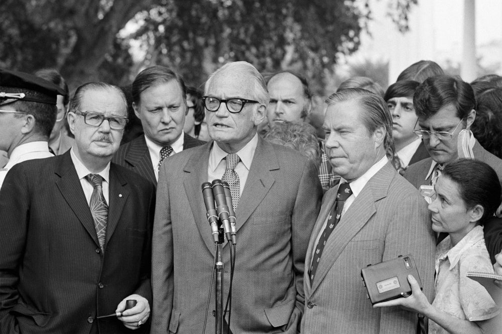 "Sen. Barry Goldwater, R-Ariz., center, speaks to reporters after meeting with President Richard Nixon at the White House to discuss Nixon's decision on resigning. Flanked by Senate Republican Leader Hugh Scott of Pennsylvania, left and House Republican Leader John Rhodes of Arizona, right, Goldwater said Nixon has made ""no decision"" on whether to resign. The three top Republican leaders in Congress paid a solemn visit to Nixon, bearing the message that he faced near-certain impeachment due to eroding support in his own party on Capitol Hill. Nixon, who'd been entangled in the Watergate scandal for two years, announced his resignation the next day."
