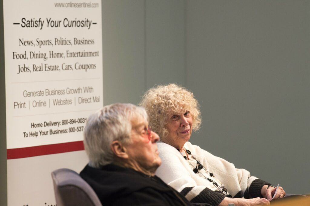Kay Joly Devine looks at her husband, J.P. Devine, as they prepare to take questions from the audience at Community Voices at Ostrove Auditorium at the Diamond Building at Colby College in Waterville on March 26, 2019.