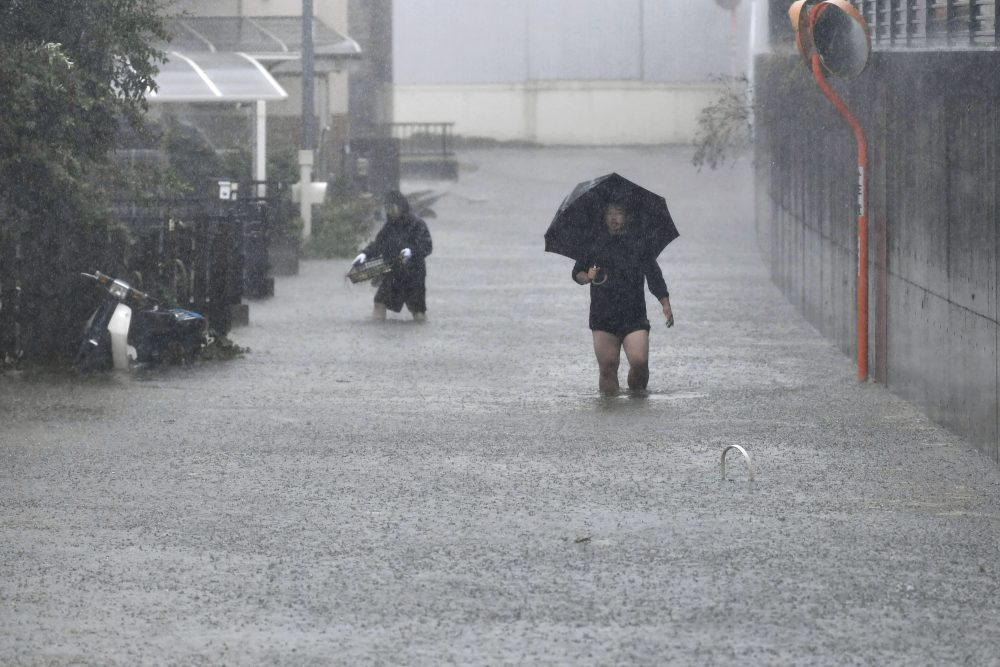 People walk through a flooded street Saturday in Shizuoka, in central Japan. As Typhoon Hagibis slams the region, more than 1,660 flights have been canceled.