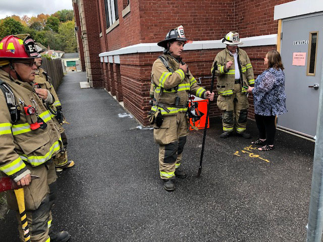 Waterville Fire Chief Shawn Esler, at right in white helmet, talks to KVCAP executive assistant Wanda Steward before firefighters left the scene Friday. Firefighters were called to KVCAP to investigate a possible gas leak.