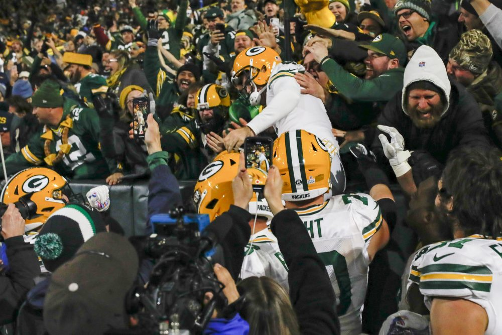Green Bay kicker Mason Crosby celebrates kicking the game-winning field goal by jumping in the stands . The Packers defeated the Lions, 23-22.