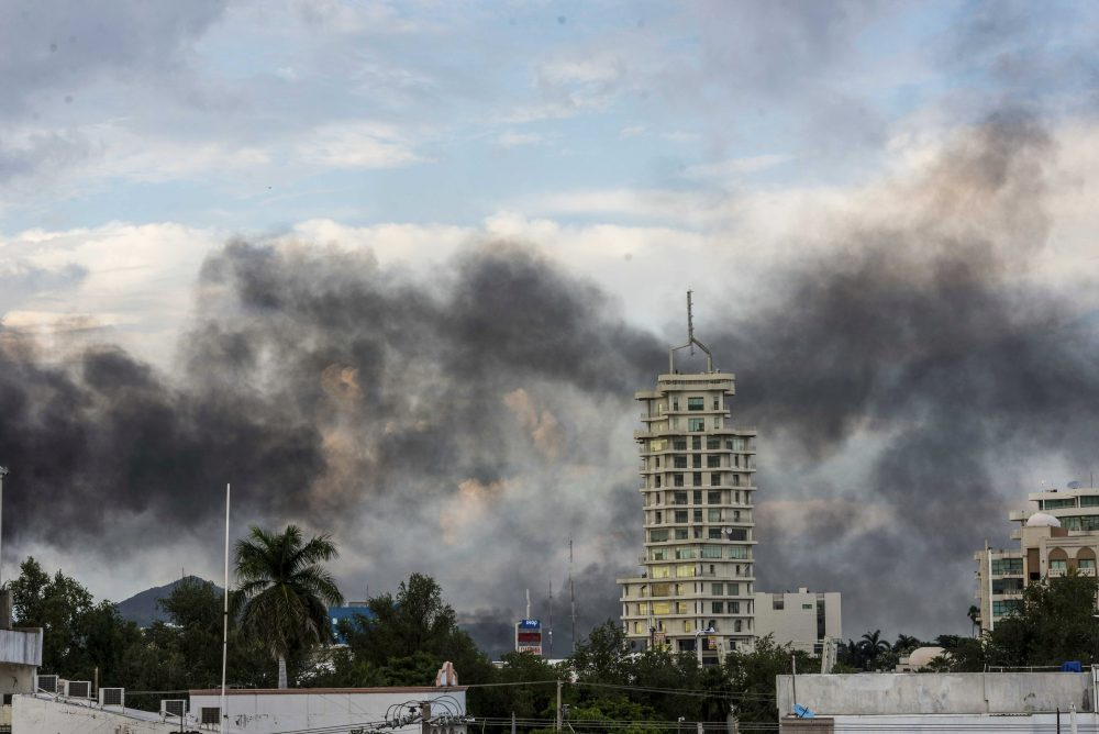"Smoke from burning cars rises in Culiacan, Mexico, on Thursday. An intense gunfight with heavy weapons and burning vehicles blocking roads raged in the capital of Mexico's Sinaloa state after security forces located one of Joaquín ""El Chapo"" Guzmán's sons, who is wanted in the U.S. on drug trafficking charges."