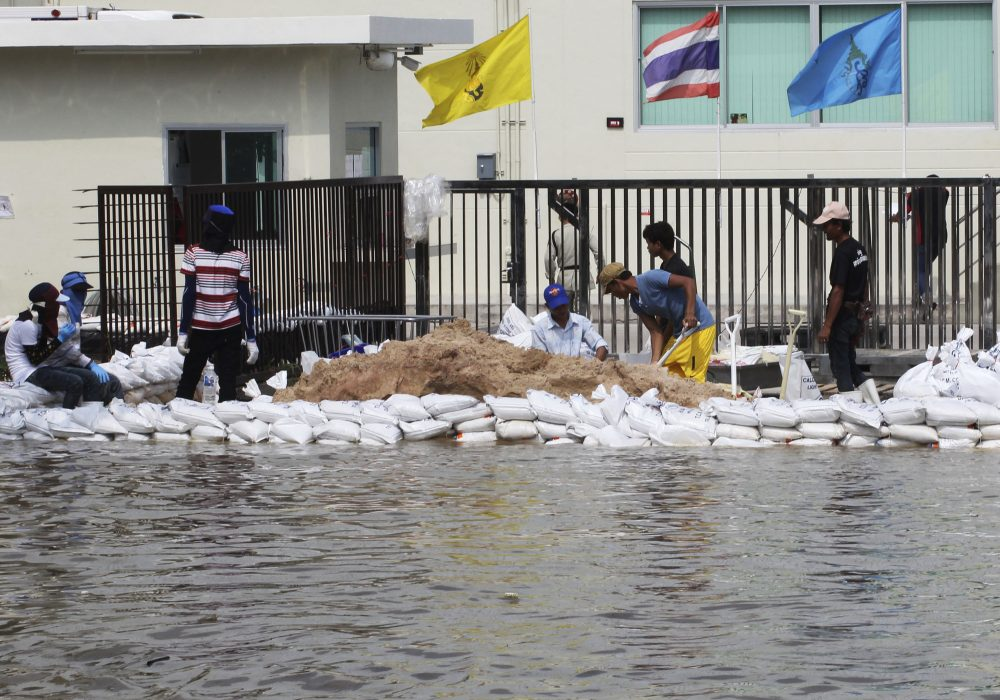 FILE - In this Oct. 9, 2013, file photo, Workers build a water barrier with sandbags as floodwater threatens their factory at Amata Nakorn industrial estate in Chonburi province, eastern Thailand, in 2013.