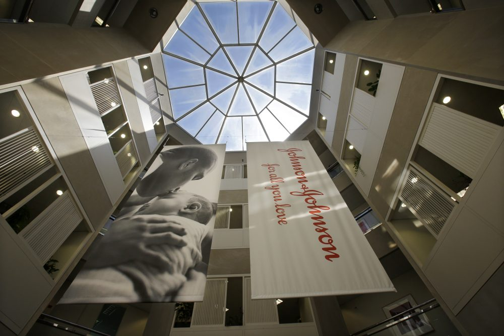 Large banners hang in an atrium at the headquarters of Johnson & Johnson in New Brunswick, N.J. Johnson & Johnson has become the latest company to settle a lawsuit to get out of the first federal trial over the nation's opioids crisis, reaching a deal worth more than $20 million with two Ohio counties, the company announced Tuesday.