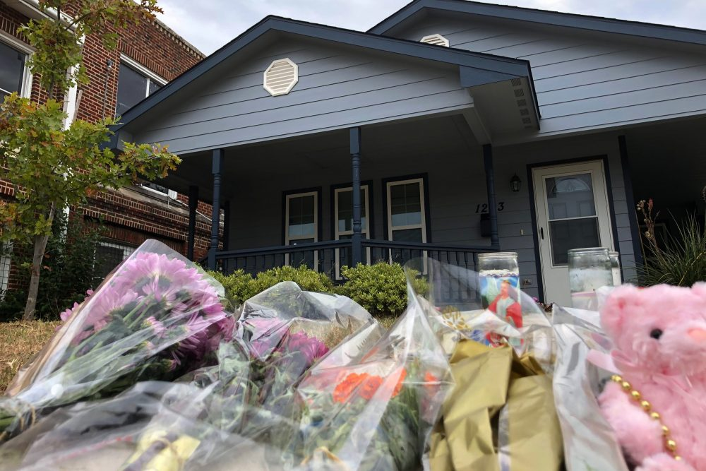 Bouquets of flowers and stuffed animals are piled up outside the Fort Worth home Monday where a 28-year-old black woman was shot to death by a white police officer.