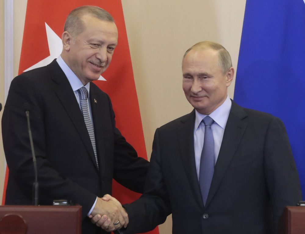 Russian President Vladimir Putin, right, and Turkish President Recep Tayyip Erdogan shake hands after their joint news conference following their talks in the Bocharov Ruchei residence in the Black Sea resort of Sochi, Russia, on Tuesday. Erdogan says Turkey and Russia have reached a deal in which Syrian Kurdish fighters will move 18 miles away from a border area in northeast Syria within 150 hours.