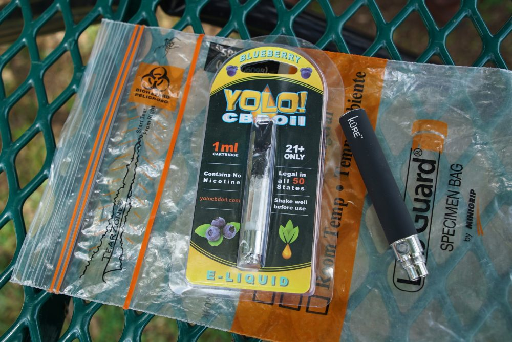 "A Yolo! brand CBD oil vape cartridge sits alongside a vape pen on a biohazard bag on a table at a park in Ninety Six, S.C. More than 50 people around Salt Lake City had been poisoned by the time the outbreak ended early last year, most by a vape called Yolo!, the acronym for ""you only live once."""