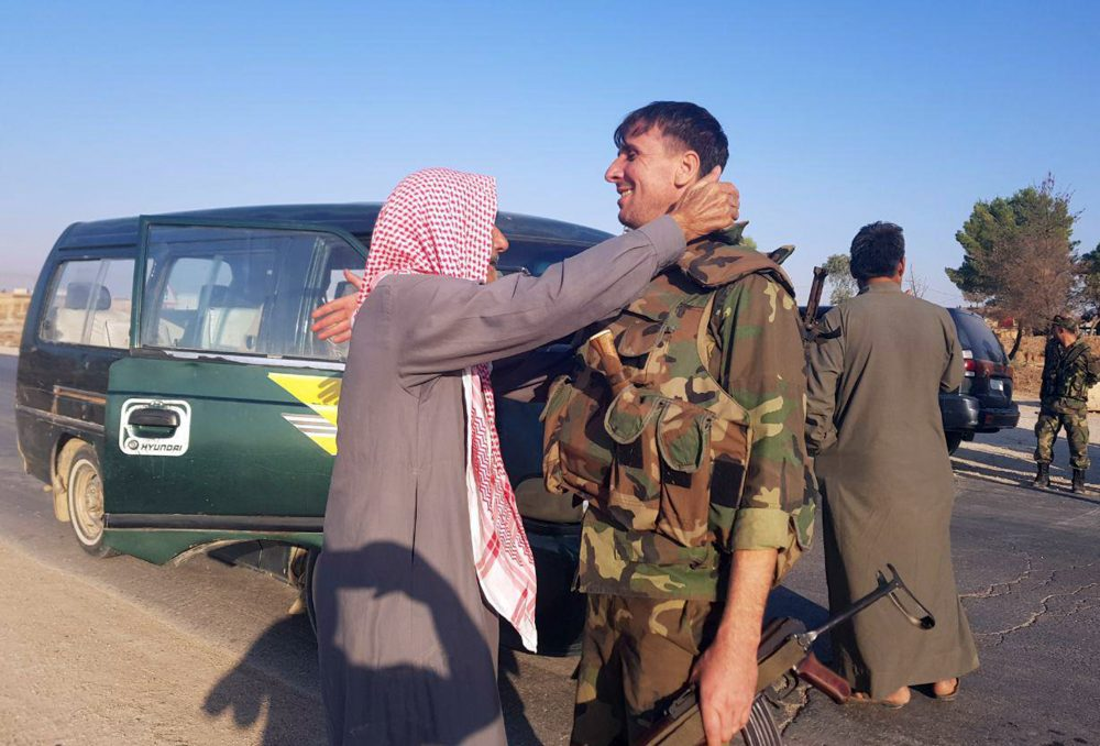 In this photo released by the Syrian official news agency SANA, a resident hugs a Syrian soldier shortly after Syrian troops entered the northern town of Tal Tamr on Monday. The move toward Tal Tamr came a day after Syria's Kurds said Syrian government forces agreed to help them fend off Turkey's invasion – a major shift in alliances that came after President Trump ordered all U.S. troops withdrawn from the northern border area amid the rapidly deepening chaos.