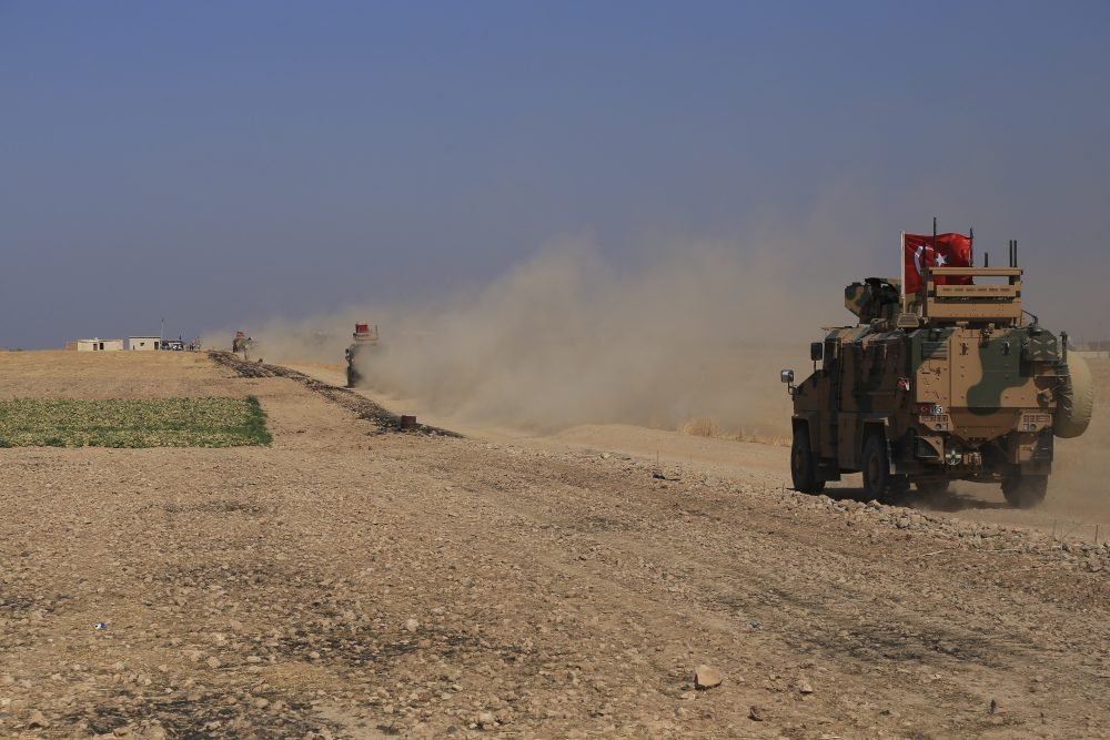"A Turkish armored vehicle patrols as part of a joint ground patrol with American forces in the so-called ""safe zone"" on the Syrian side of the border with Turkey."