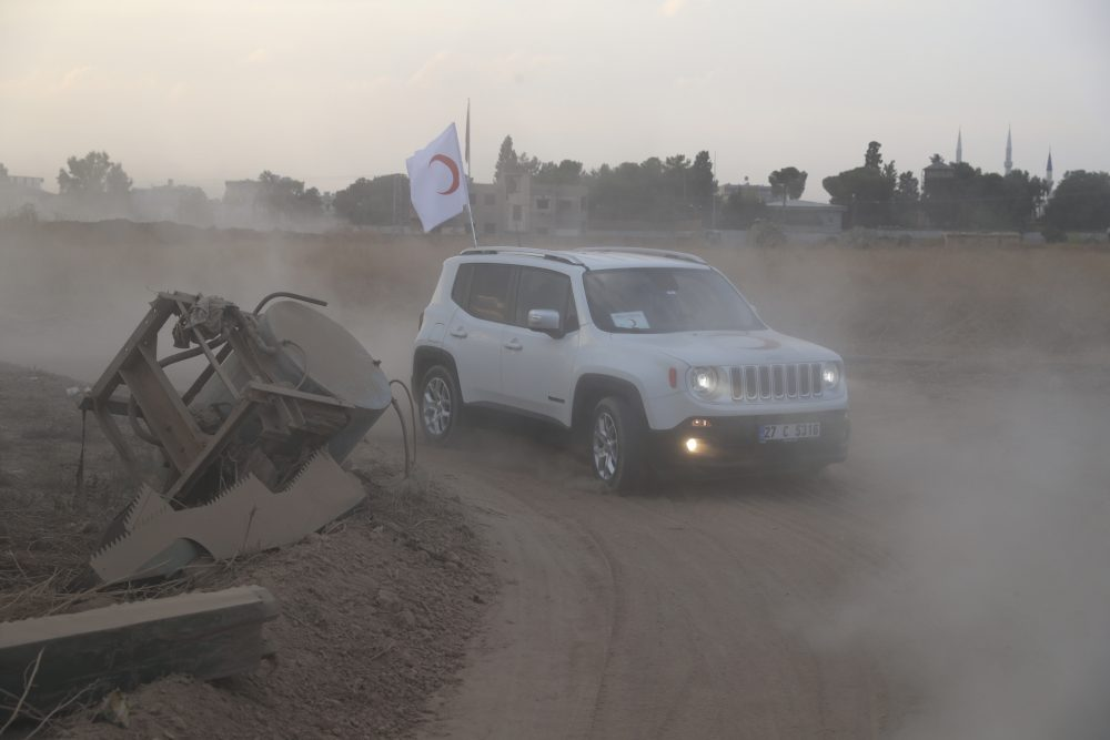 Turkish Red Crescent vehicles arrive to deliver aid to Syrians in Ras Al-Ain, Syria, on Saturday. The city was evacuated on Sunday, a spokesman for the Kurdish-led Syrian Democratic Forces said.
