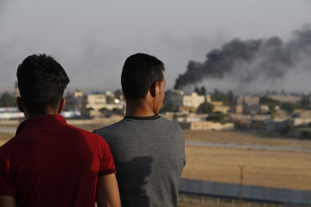 People standing on a rooftop in Akcakale, Sanliurfa province, southeastern Turkey, at the border with Syria, watch as smoke billows from fires caused by Turkish bombardment in Tal Abyad, Syria, on Sunday.