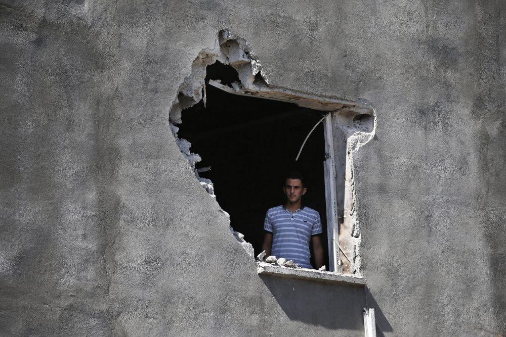 """A resident looks out from a hole in a house that was damaged by a mortar fire in the Turkish town of Akcakale on Saturday. President Trump has withdrawn U.S. forces in Syria, saying he wanted to stop getting involved with """"endless wars."""""""