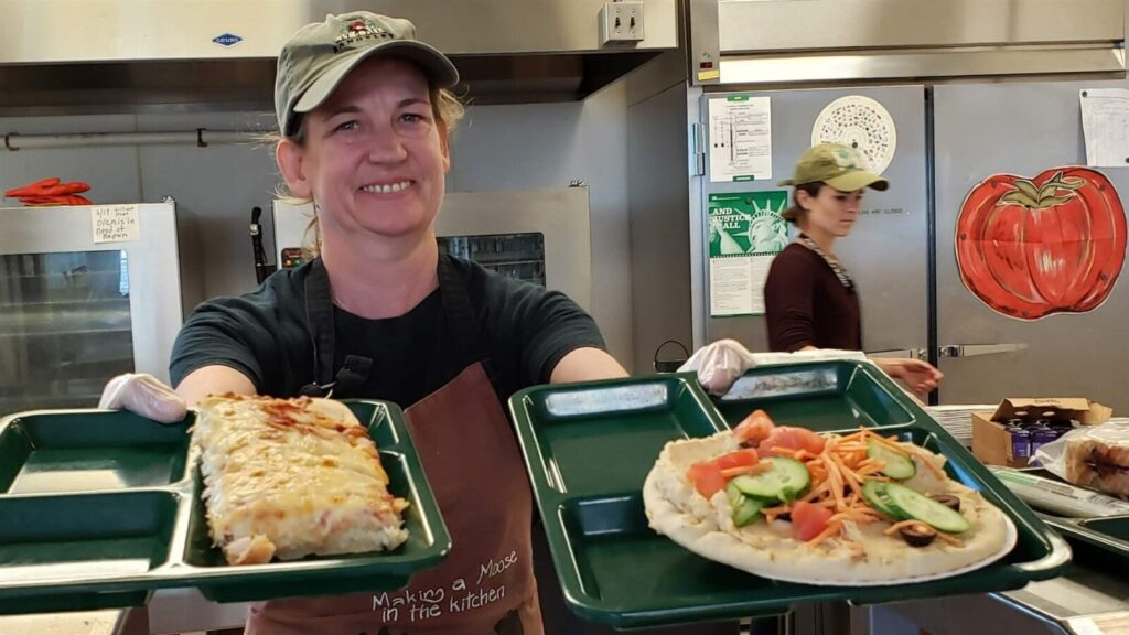 Portland school cafeteria worker Alison Mason shows off lunch options at East End Community School, including traditional pizza, left, and vegan pizza with hummus and vegetables. More schools are adopting vegan lunches, but a bill to allocate $3 million for plant-based lunch options is stalled in the California legislature.