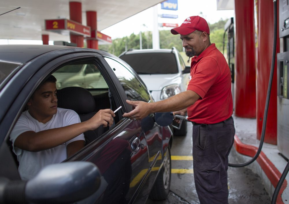 Gas station attendant Leowaldo Sanchez takes a cigarette as payment from a motorist as he fills the tank in San Antonio de los Altos, Venezuela, on Oct. 8. This barter system, while perhaps the envy of cash-strapped drivers outside the country, is just another symptom of bedlam in Venezuela where a full tank these days costs a tiny fraction of a U.S. penny.