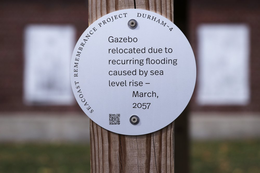 A sign, part of a public design installation by artist Thomas Starr, is displayed on a gazebo outside the University of New Hampshire boathouse in Durham, N.H. Starr, a graphic and information design professor from Boston's Northeastern University, created the project to address possible effects of climate change.