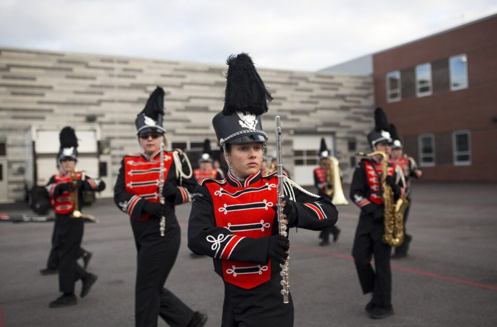 Less than an hour before state finals, eighth-grader and flute player Katie Dallaire practices steps with the band behind Sanford High.