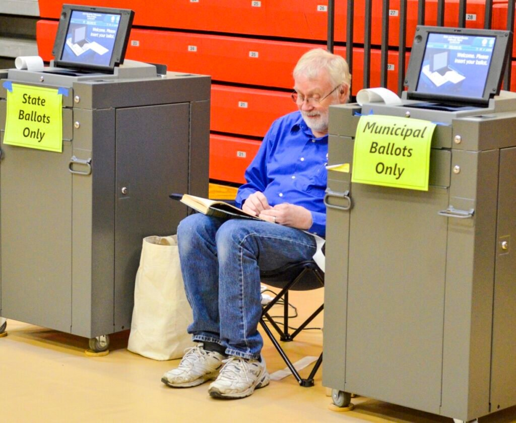 Flanked by voting machines, poll worker Harold Booth reads a book during a quiet moment Tuesday at Hall-Dale Elementary School in Hallowell.