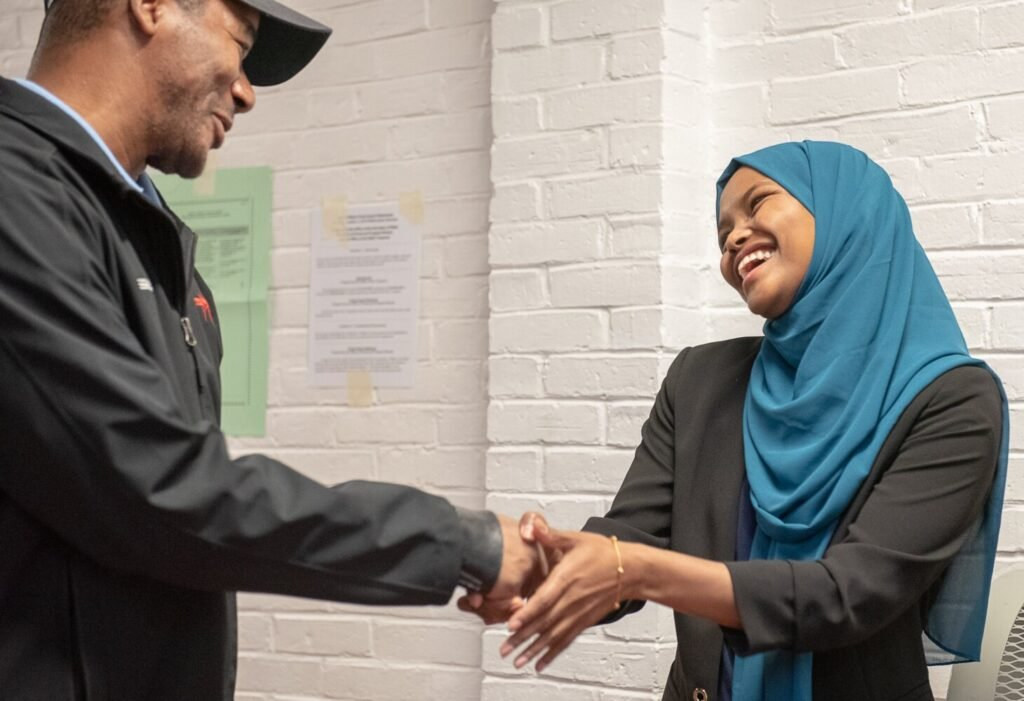 Lewiston City Council Ward 1 candidate Safiya Khalid greets a voter at the Lewiston Armory on Tuesday morning.