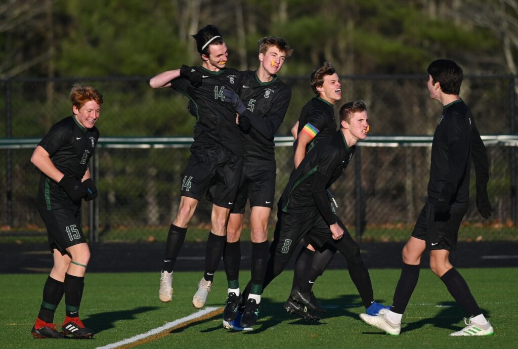 Waynflete's Joey Ansel-Mullen (14) celebrates with teammates, including Harry Millispaugh (5) after scoring the game's first gaol against Mount View in the Class C state championship Saturday in Falmouth.