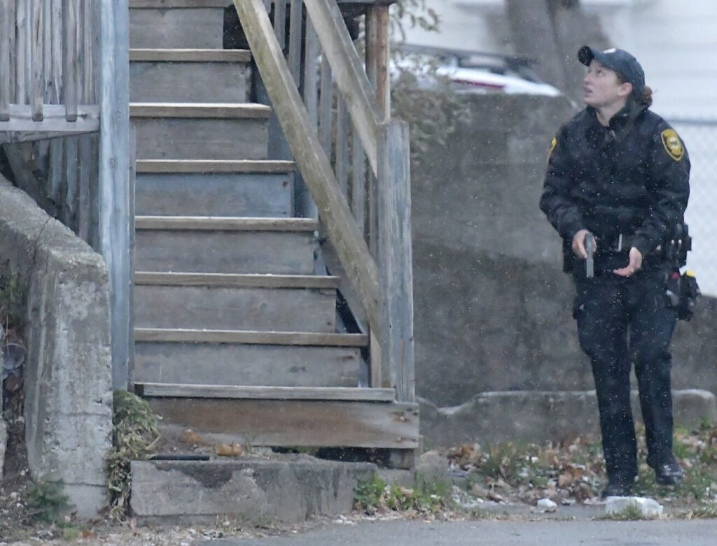 An Augusta police officer approaches 93 Northern Ave. on Monday after police received a report of gunfire at the building.