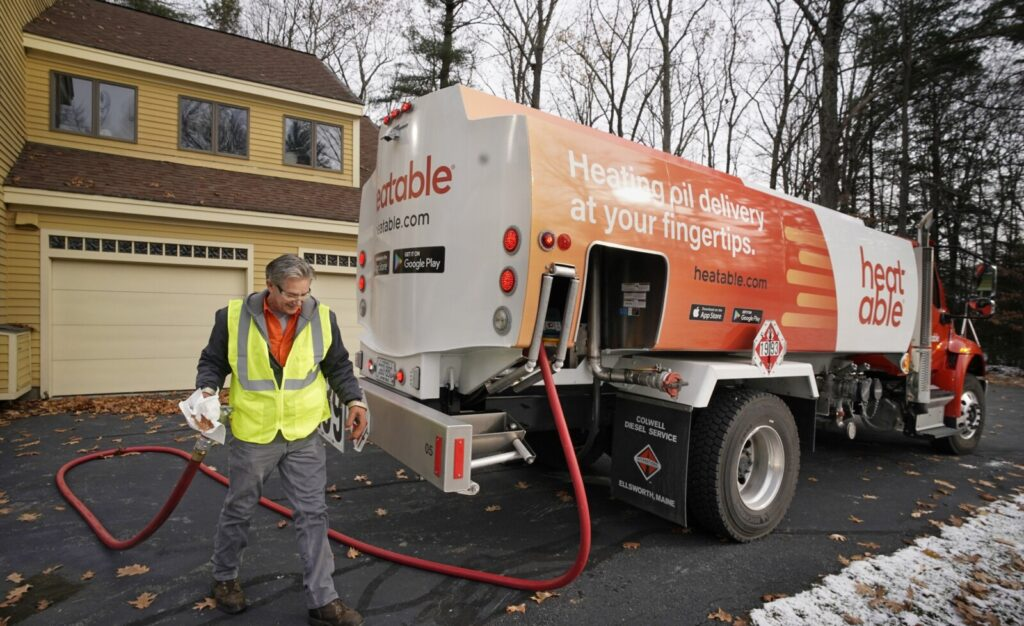 Fred Cyr, a driver for Heatable, walks a hose back to the side of a delivery truck while delivering oil to a home in Falmouth last week. Heatable is one of two new oil delivery companies in southern Maine that offer ordering online or on a smartphone app, competing with traditional oil companies with low prices and rapid delivery.
