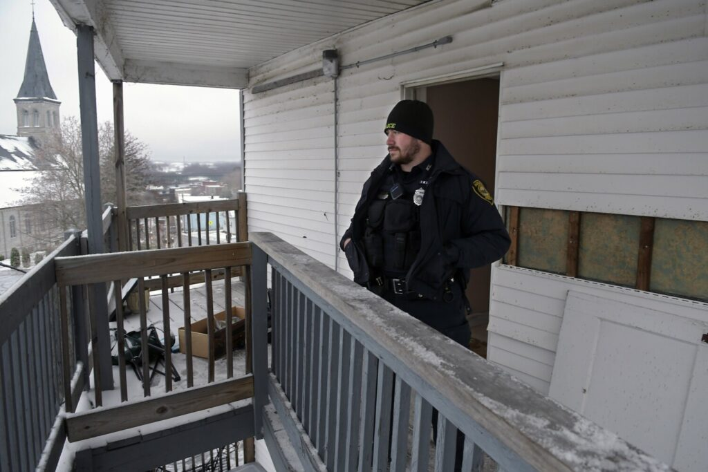 Augusta Police Officer Desmond Nutting stands Tuesday at the third floor entrance of 93 Northern Ave. in Augusta. Two bodies were recovered Monday in an apartment at the building. The structure is across the street from St. Michael Parish.