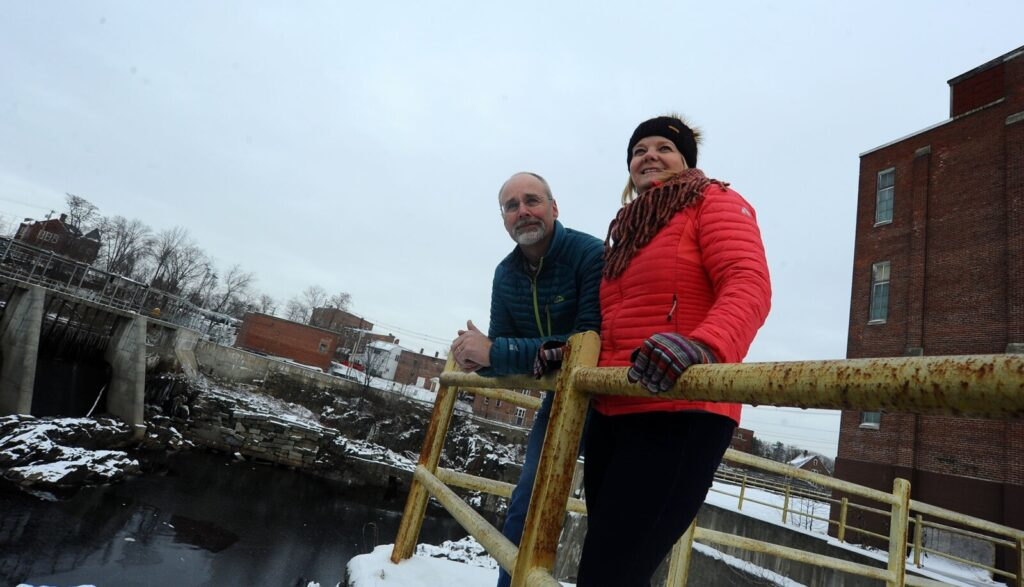 Jeff and Pam Powers of Bigelow Brewing are pictured Nov. 14, 2019, between the former Solon Manufacturing building at 7 Island Ave. in Skowhegan, right, and the Kennebec River, left.