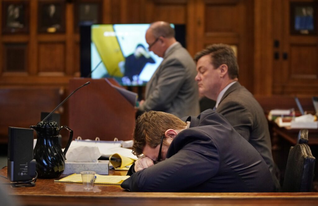 Noah Gaston listens with his head in his hands as a video interview plays during the second day of his trial in Cumberland County Superior Court on Thursday. Gaston is charged with murder and manslaughter in the shooting death of his wife, Alicia Gaston, in their Windham home in January 2016.